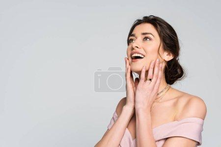 Photo pour Mariée étonnée regardant loin tout en tenant les mains près du visage isolé sur gris - image libre de droit