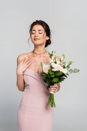 smiling woman holding wedding bouquet while standing with closed eyes isolated on grey