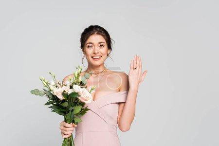 joyful woman showing wedding ring while holding flowers isolated on grey