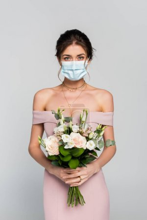 young fiancee in medical mask holding wedding bouquet isolated on grey