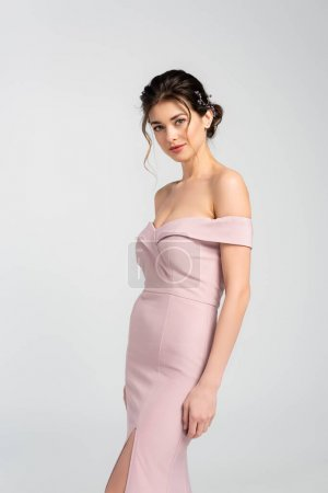 charming bride in pink, elegant dress looking at camera isolated on grey