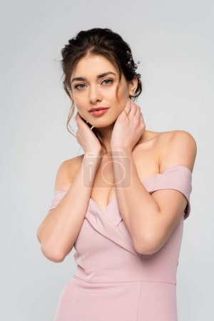 young fiancee touching neck while looking at camera isolated on grey