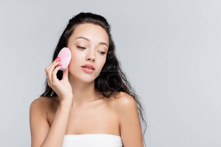 brunette young woman using cleansing brush isolated on grey