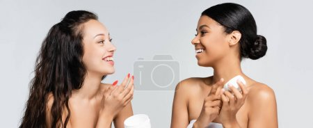 brunette multiethnic women with bare shoulders laughing while holding containers with cosmetic cream isolated on grey, banner