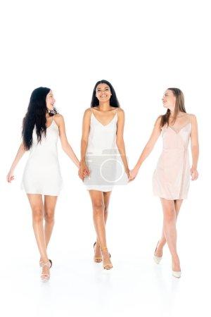 volle Länge von fröhlichen interrassischen Frauen in Kleidern, die Händchen haltend und isoliert auf weiß wandeln