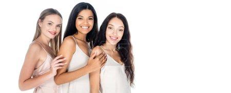 joyful interracial women in dresses smiling isolated on white, banner