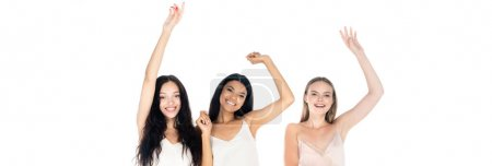 excited interracial women in dresses standing with raised hands isolated on white, banner