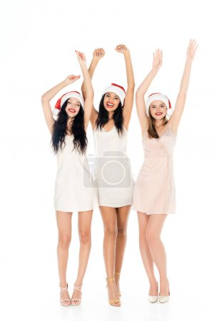 full length of cheerful interracial women in santa hats and dresses standing with raised hands isolated on white