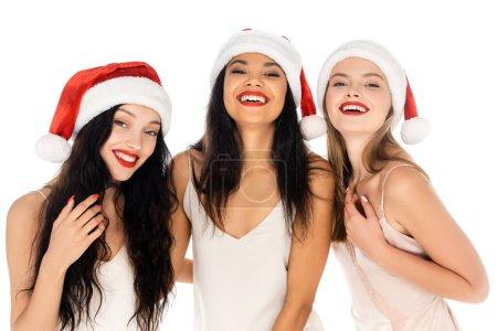 Photo pour Souriant interracial femmes dans santa chapeaux et robes isolé sur blanc - image libre de droit