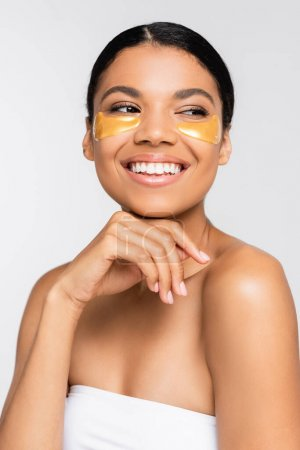 brunette african american woman in collagen eye patches smiling isolated on white