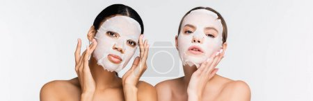 young multiethnic women in moisturizing sheet masks isolated on white, banner