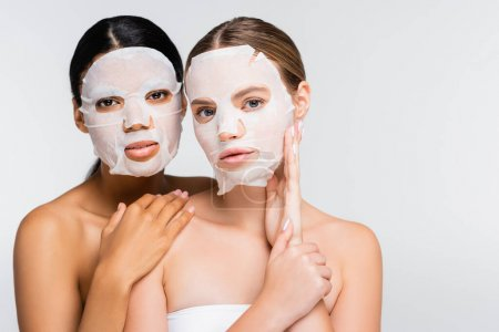 interracial women in moisturizing sheet masks isolated on white