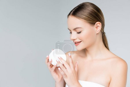 Photo for Cheerful young woman holding container with face cream isolated on grey - Royalty Free Image
