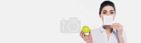 Young woman holding card with smile sign and apple isolated on white, banner