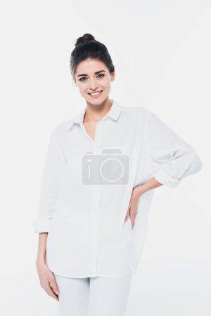Mujer joven en camisa blanca sonriendo a la cámara aislada en blanco