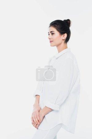 Junge brünette Frau im Hemd schaut isoliert auf weißem Grund weg