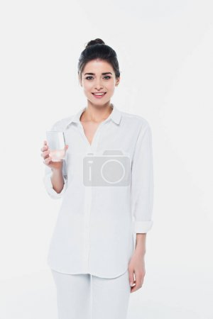 Smiling woman in white shirt holding glass of water isolated on white