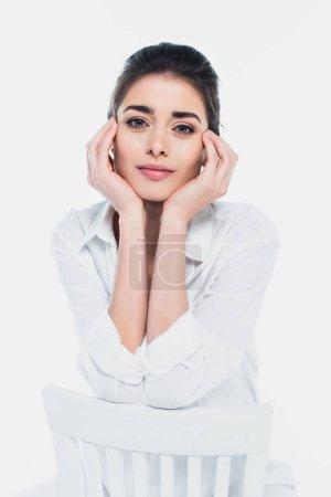 Junge Frau mit händchennahem Gesicht blickt in die Kamera auf Stuhl isoliert auf weiß
