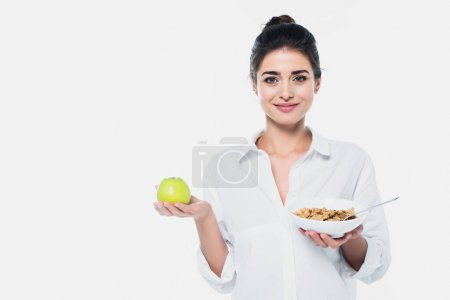Smiling woman holding fresh apple and bowl of cereals isolated on white