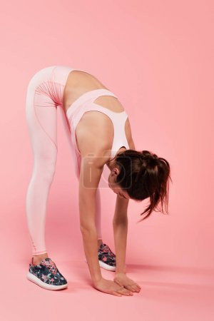 Young sportswoman stretching on pink background