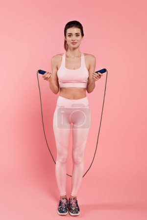 Positive sportswoman holding jump rope on pink background