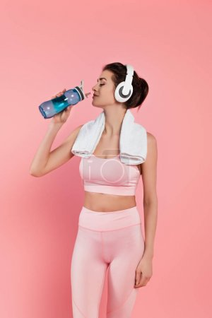 Sportswoman with headphones and towel drinking water isolated on pink