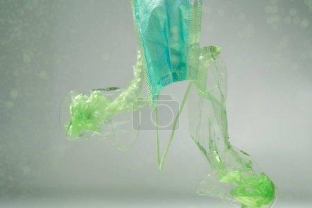 envases de plástico y tazas cerca de máscara médica bajo el agua, concepto de ecología