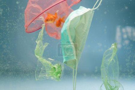 Netz mit Goldfischen, medizinischer Maske, Plastiktüten und Bechern im Wasser, ökologisches Konzept