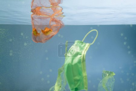 protective mask near net with goldfishes in water, ecology concept