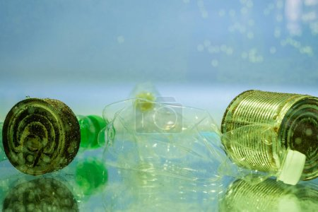 plastic bottles and rusty cans in water, ecology concept
