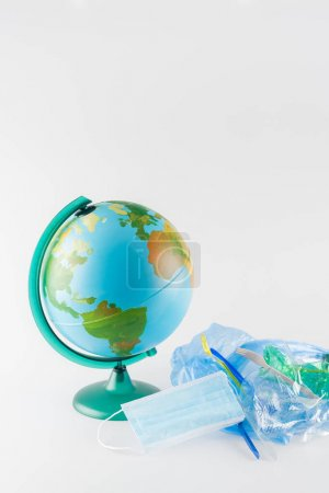 globe near cellophane bag with plastic rubbish on grey, ecology concept