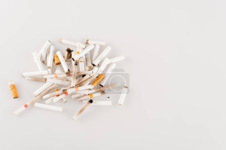 Photo pour Beaucoup de extrémités de cigarette sur la surface blanche, concept écologique, vue de dessus - image libre de droit