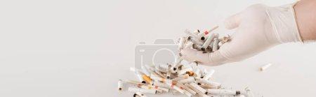 abgeschnittene Ansicht der männlichen Hand in Latexhandschuhen in der Nähe von Zigarettenenden auf weiß, Umweltkonzept, Banner