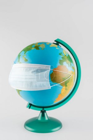 protective mask on earth globe isolated on grey, ecology concept