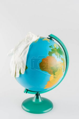 latex gloves on globe isolated on grey, ecology concept