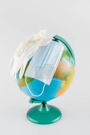 medical mask and latex gloves on globe isolated on grey, ecology concept