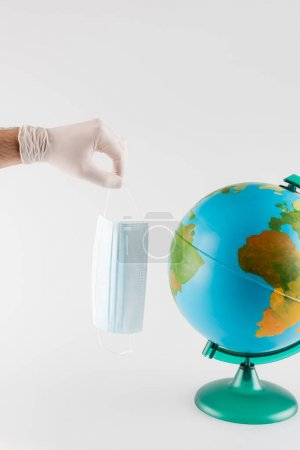 globe near man in latex glove holding medical mask isolated on grey, cropped view, ecology concept
