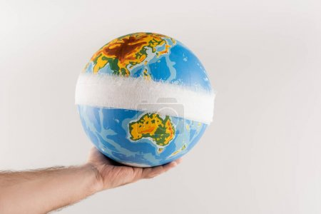 partial view of man holding bandaged globe isolated on grey, ecology concept