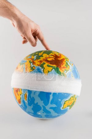cropped view of man touching bandaged globe on grey, ecology concept