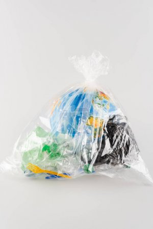 Photo for Globe packed in cellophane bag with plastic rubbish on grey, ecology concept - Royalty Free Image