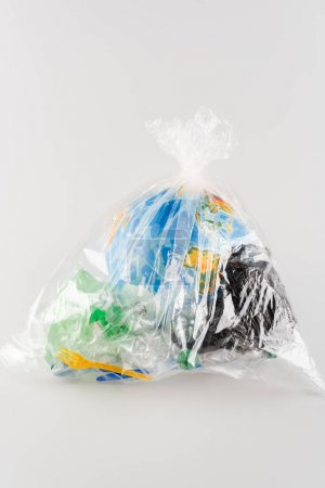 globe packed in cellophane bag with plastic rubbish on grey, ecology concept