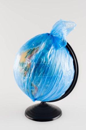 Globus verpackt in Plastiktüte isoliert auf grau, ökologisches Konzept