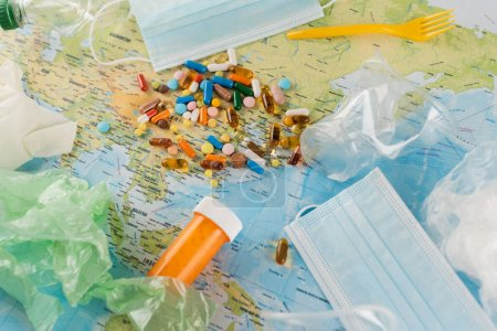 Photo for Top view of plastic garbage, medical masks and pills on map, ecology concept - Royalty Free Image