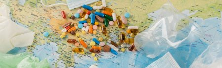 pills near medical masks and plastic rubbish on map, ecology concept, banner