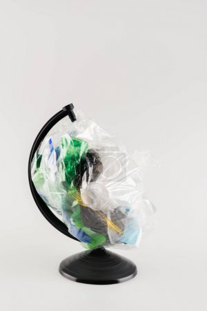 cellophane pack with plastic garbage on globe stand isolated on grey, ecology concept