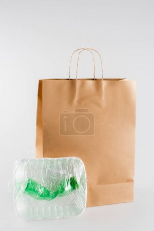 plastic plate and bottle packed in cellophane near paper bag on grey, ecology concept