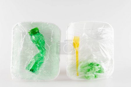 top view of plastic plates with bottle and fork packed in polyethylene, ecology concept