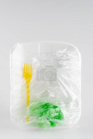 Photo pour Vue du dessus de la plaque en plastique, fourchette et sac emballés dans du cellophane, concept écologique - image libre de droit