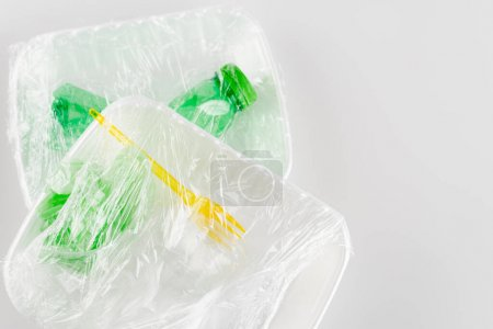 top view of plastic plates with fork and bottle packed in cellophane, ecology concept