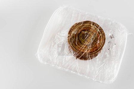 Photo pour Vue de dessus de l'étain rouillé sur plaque en plastique emballé dans du cellophane, concept d'écologie - image libre de droit